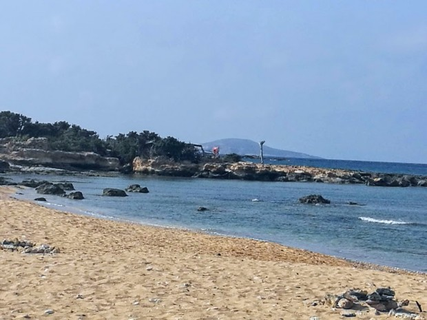 В далечината се вижда двуетажният заслон на плажа Лавракас